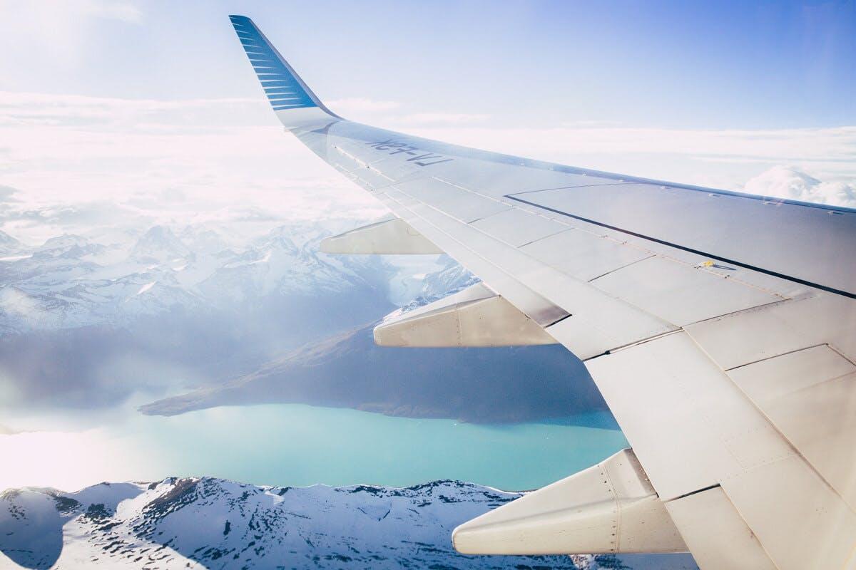 Flugzeug-Flügel über den schneebedeckten Alpen