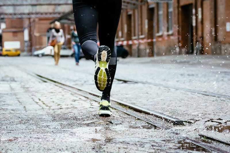 Läufer auf der Straße im Regen