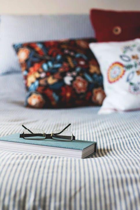 Buch, Lesebrille und bequeme Kissen