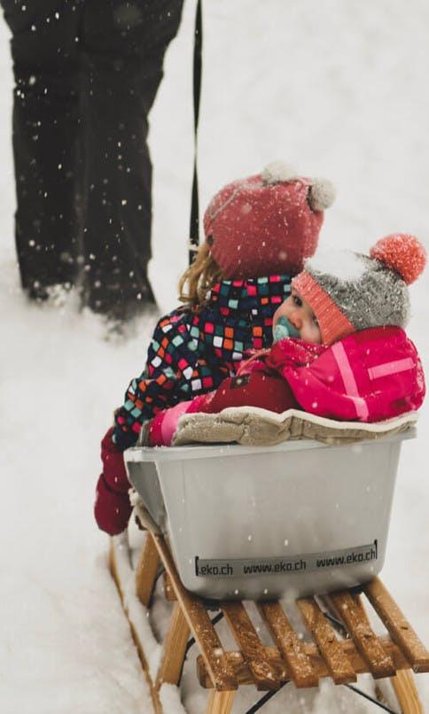 Kinder am Schlitten im Schnee