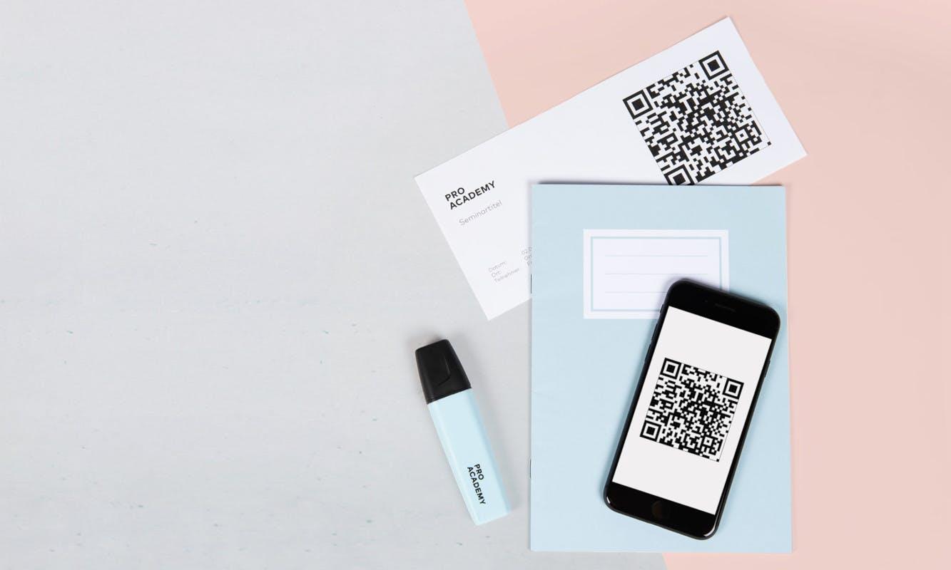 QR-Code auf einem Handy und Notizheft