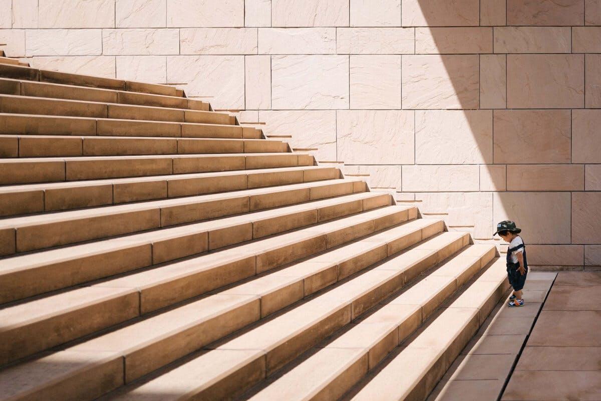 Ein Junge steht vor den Stufen zum Erfolg
