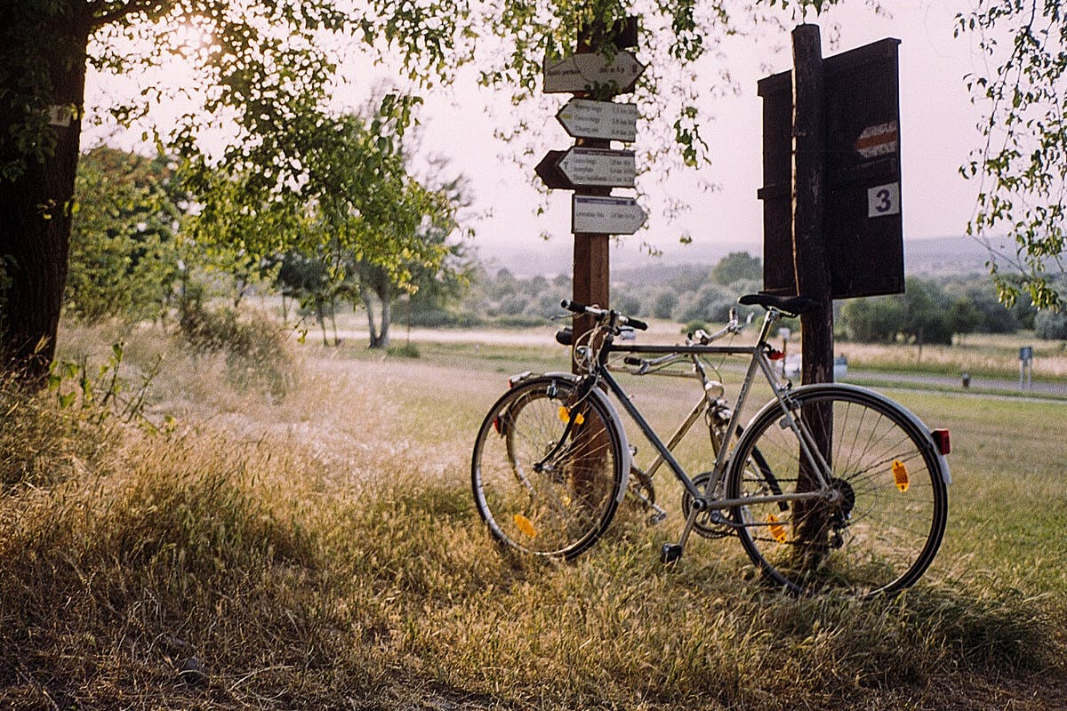 Fahrrad lehnt an einem Wegweiser
