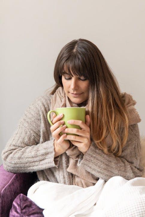 Immunsystem unterstützen, Frau mit Teesasse auf der Couch