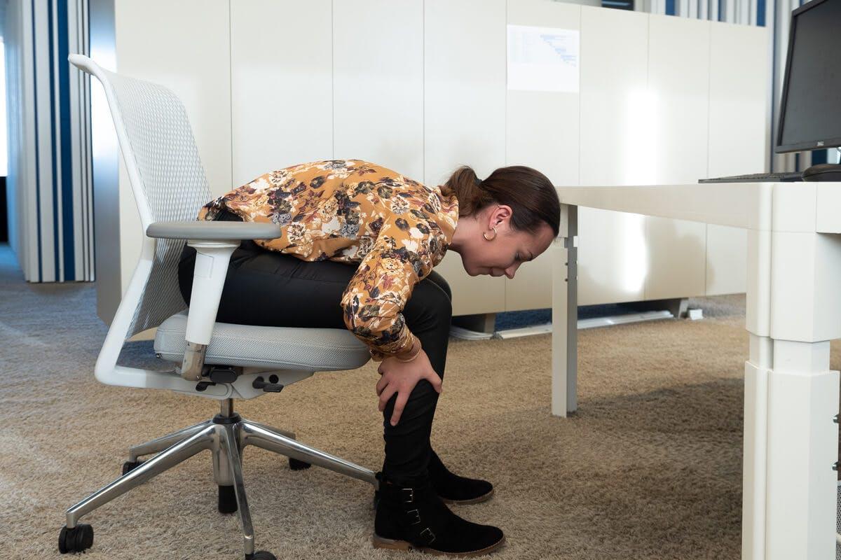 Frau dehnt ihren Rücken im Bürostuhl