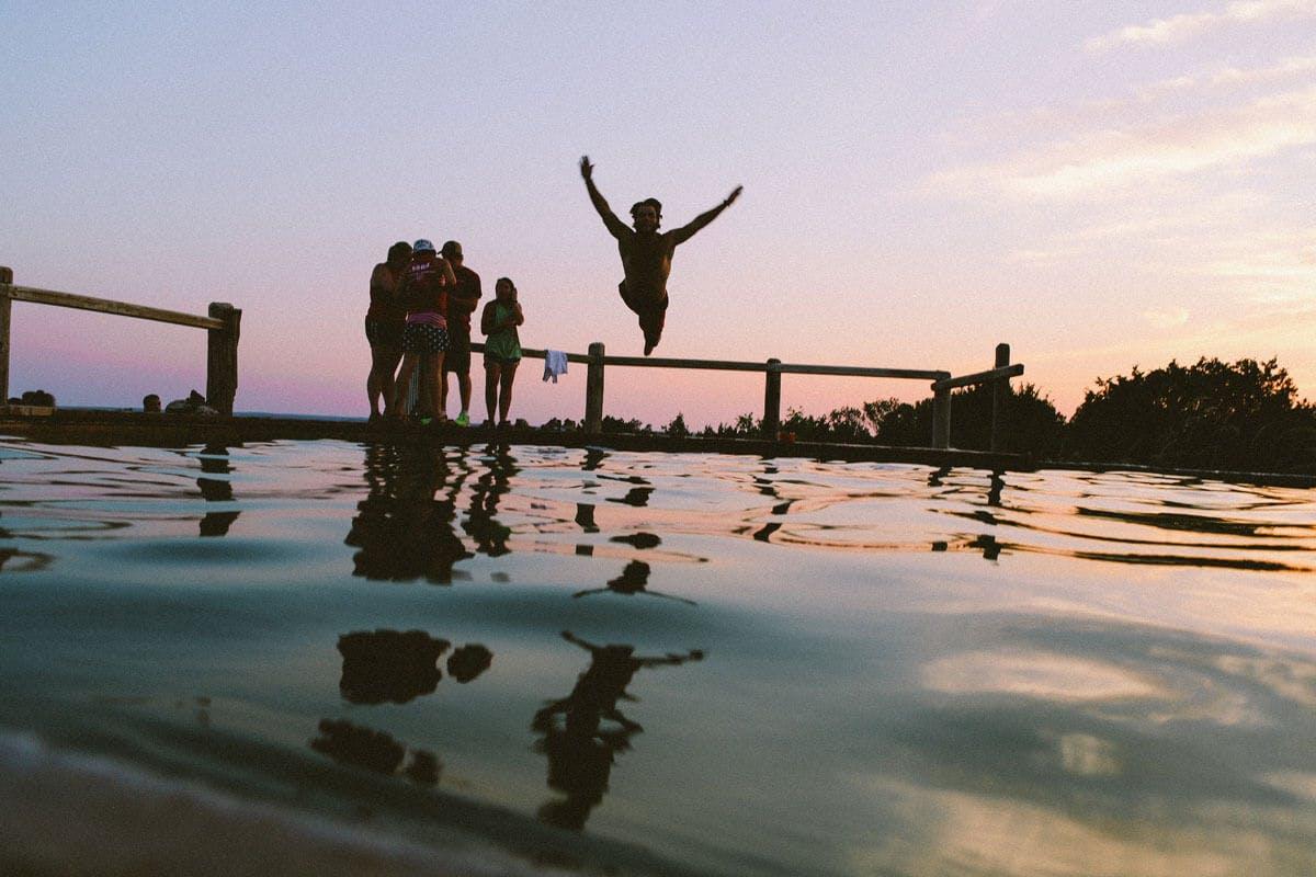 Mann springt technisch gekonnt ins Wasser