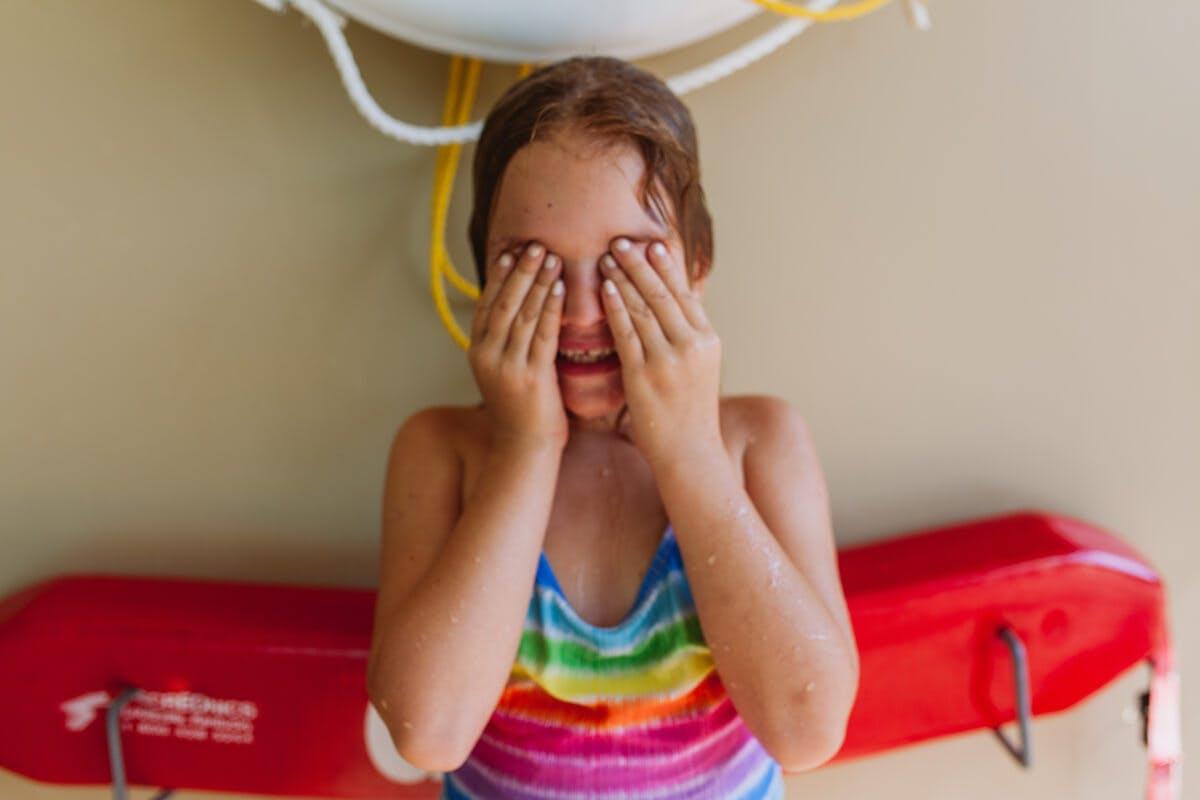 Mädchen im Badeanzug wischt sich Wasser aus den Augen