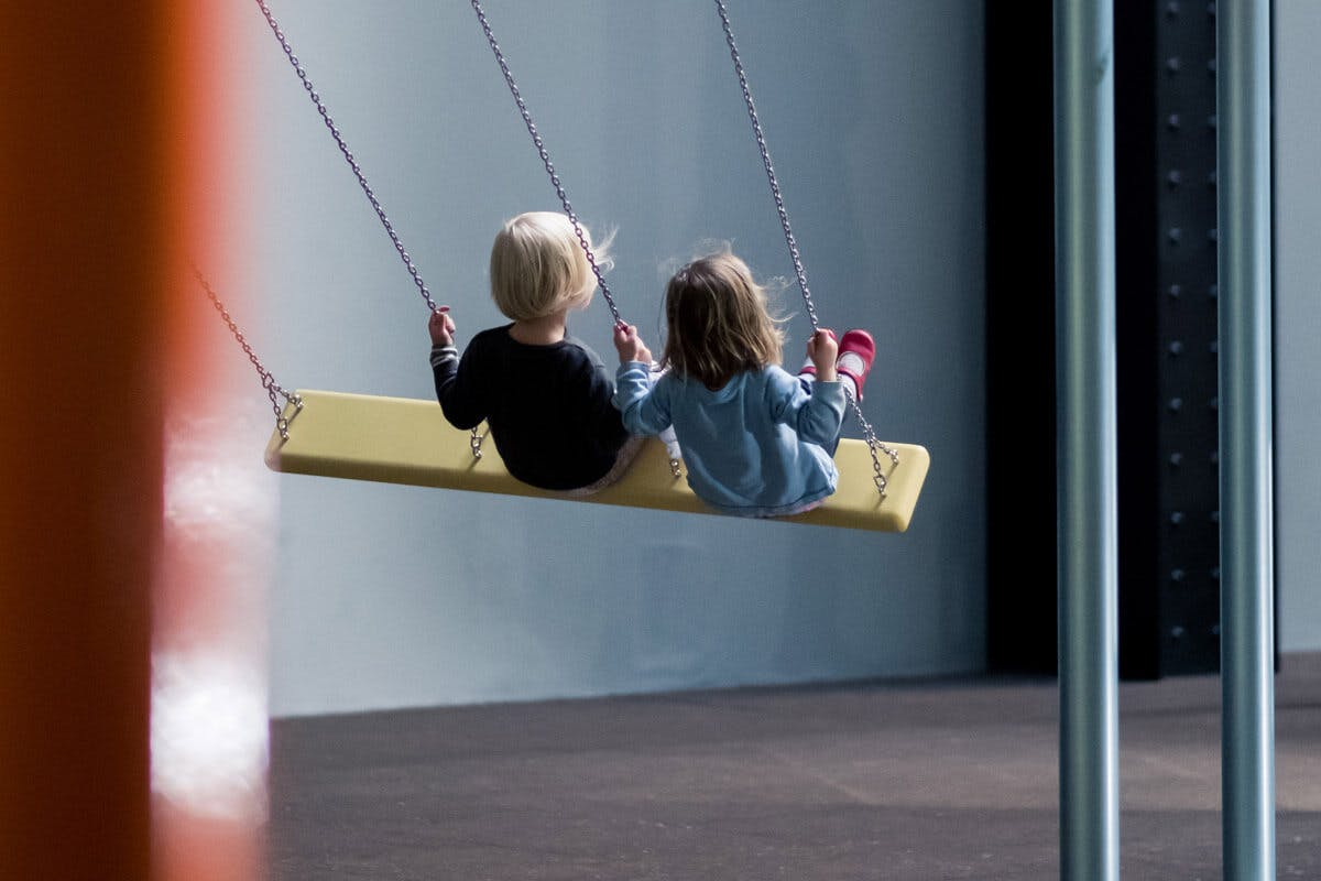 Kinder auf Schaukel am Indoor-Spielplatz