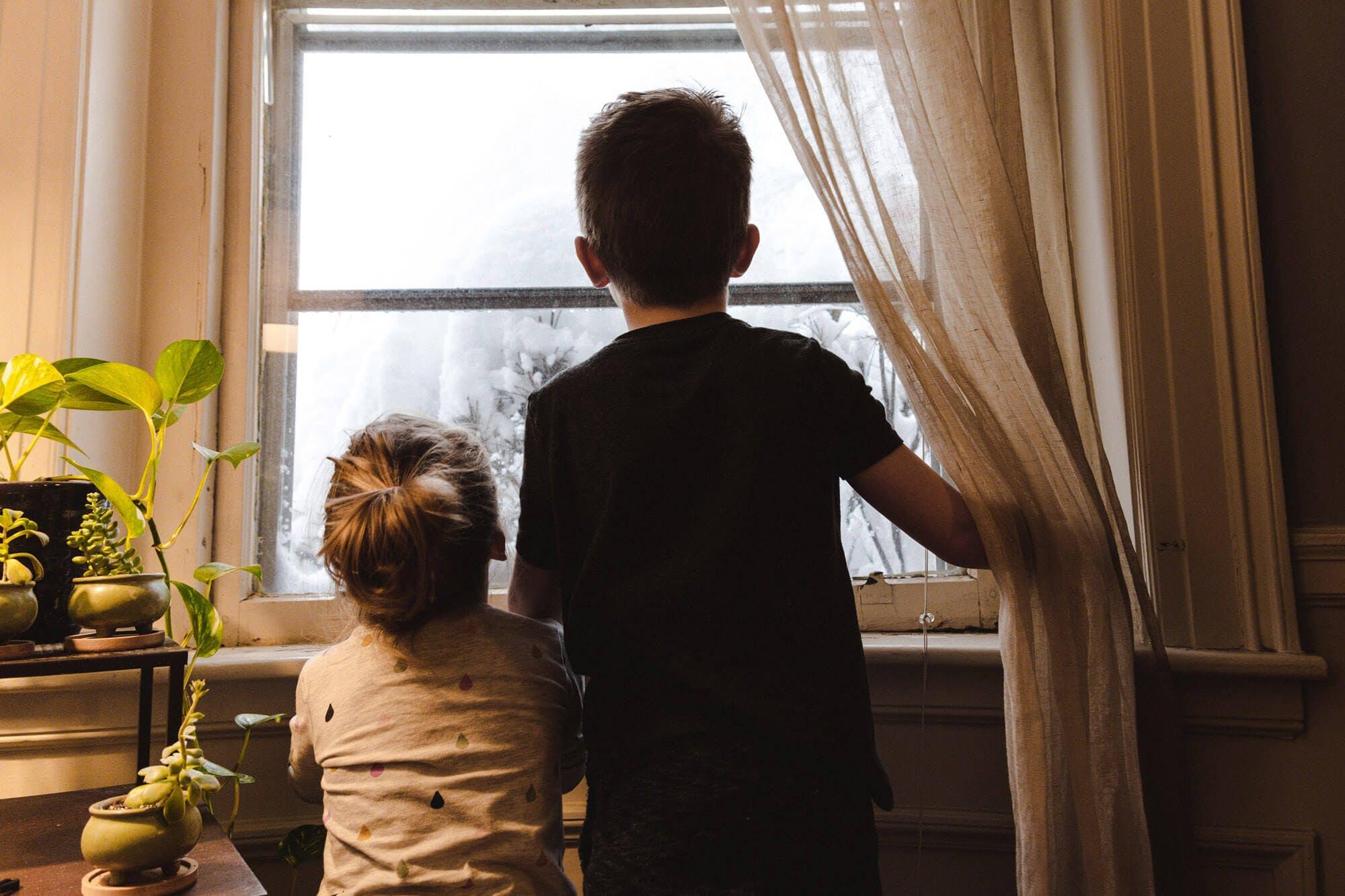 Kinder schauen im Winter aus dem Fenster
