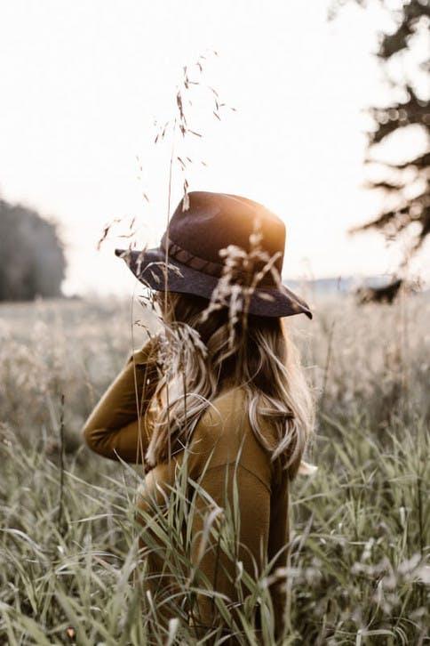 Mädchen mit Hut steht im Feld