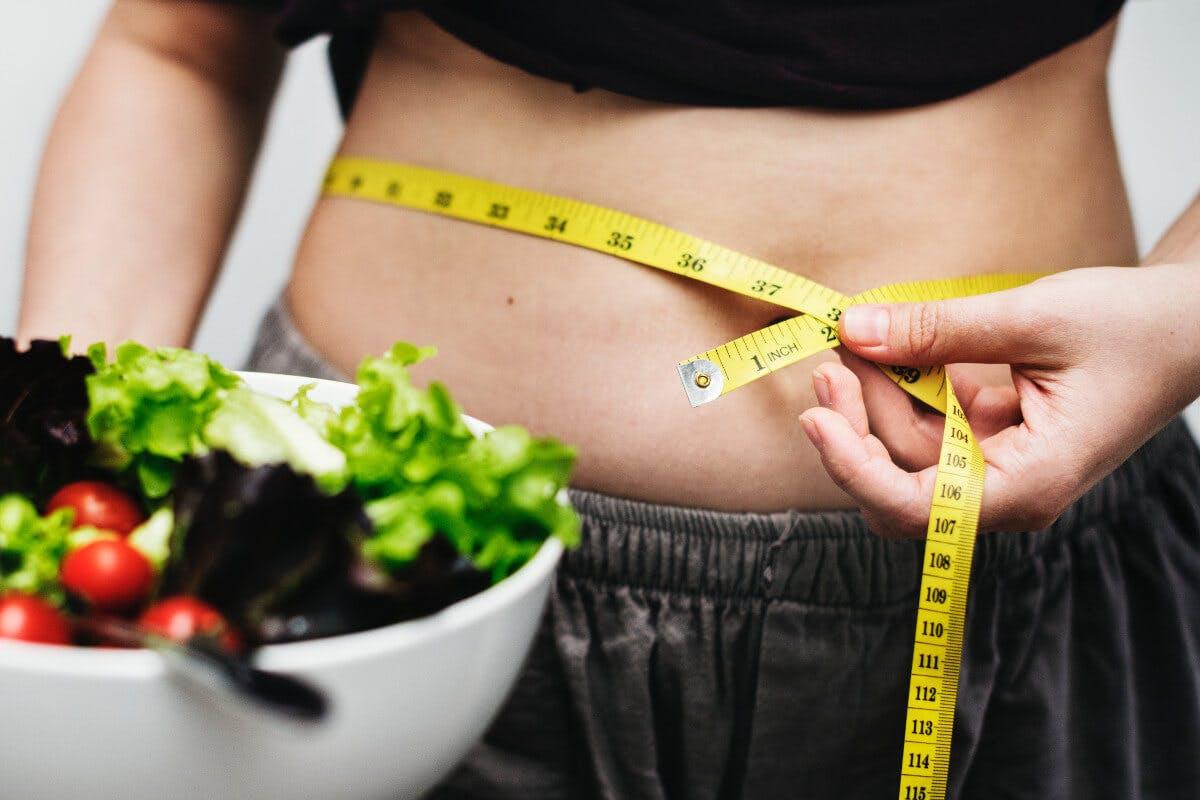 Maßband um den Bauch und Salatschüssel im Vordergrund