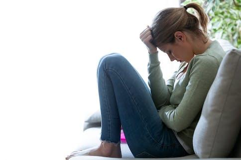 Woher kommt die Harnwegsinfektion? Frau sitzt mit Blasenschmerzen auf der Couch