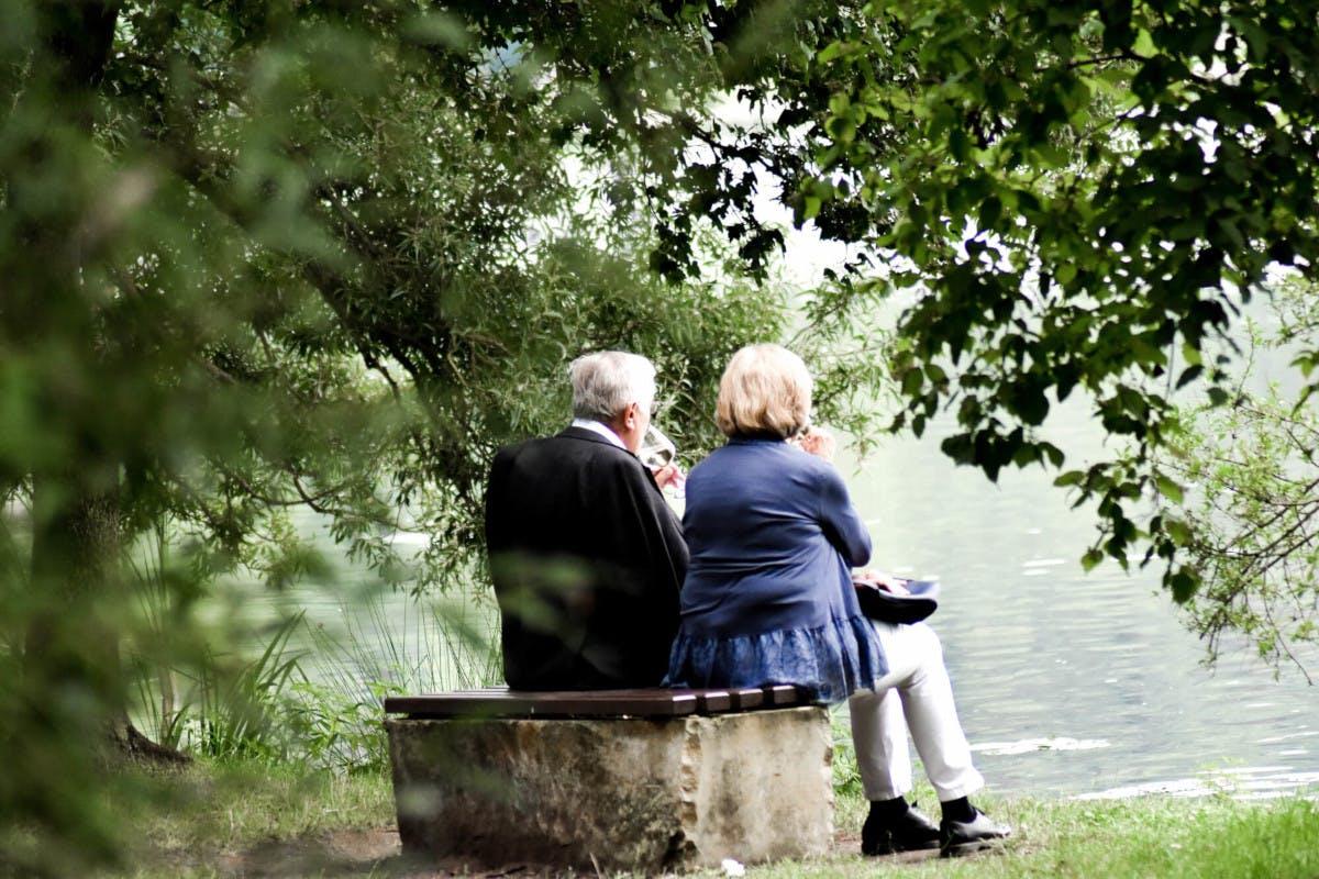 Älteres Paar sitzt vor einem See