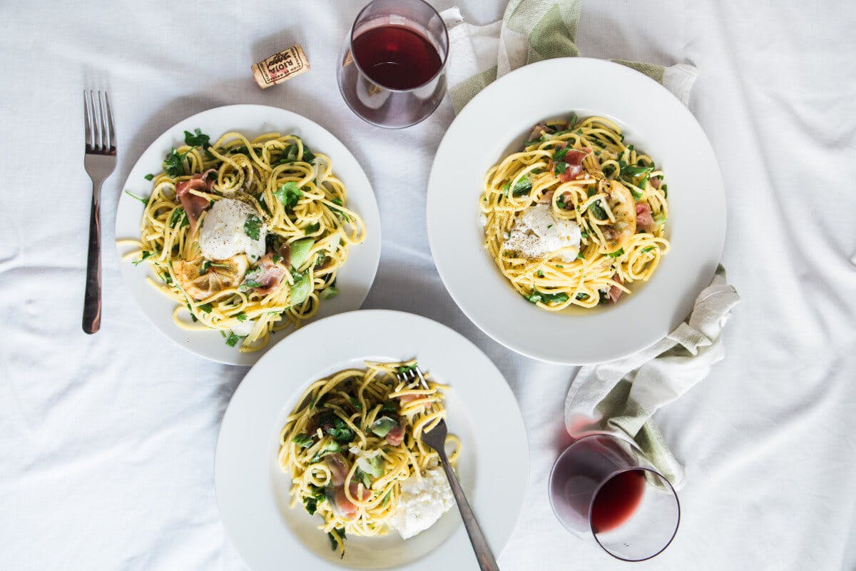 Drei Teller mit Pasta und zwei Gläser Wein