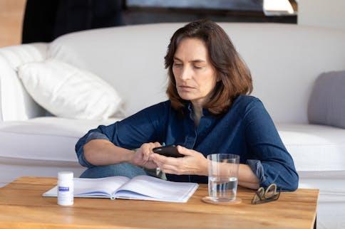 Den Wechseljahren mit Gelassenheit entgegensehen: Frau am Wohnzimmertisch mit Handy