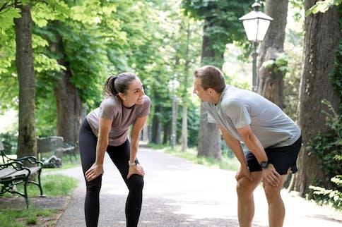 2 Läufer im Park machen eine kurze Pause, Hände auf die Oberschenkel gestützt