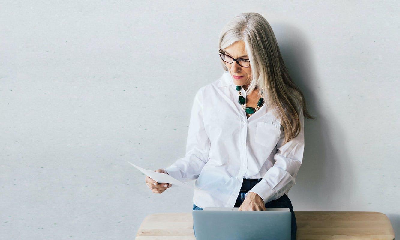 Frau tippt auf ihrem Laptop und liest einen Zettel