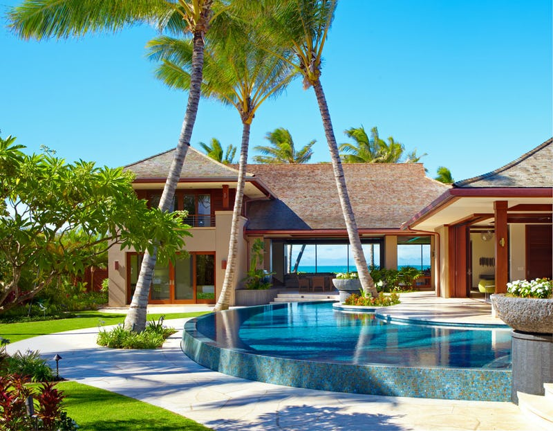 Exterior photo of house with pool and trees