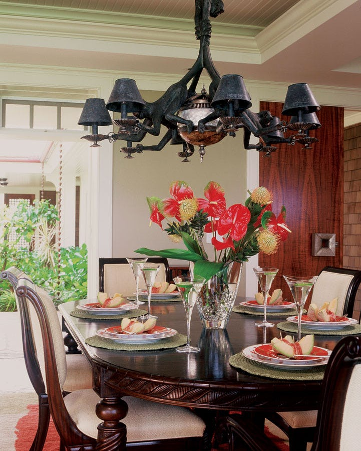 Dining area with chandelier and floral centerpiece.