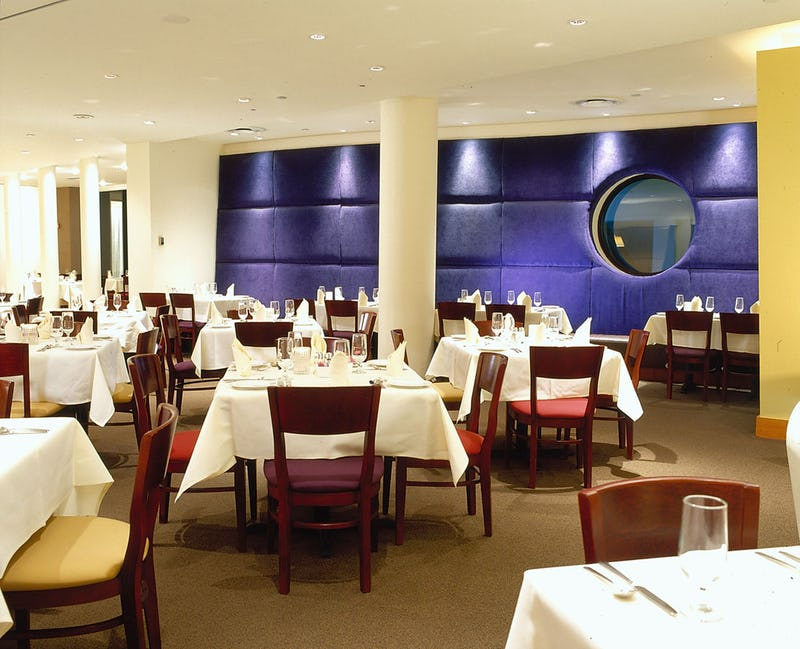 Dining tables in front of blue fabric wall at Assaggio Ristorante