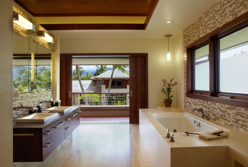 Bathroom with dual sinks and tub and doorway to balcony