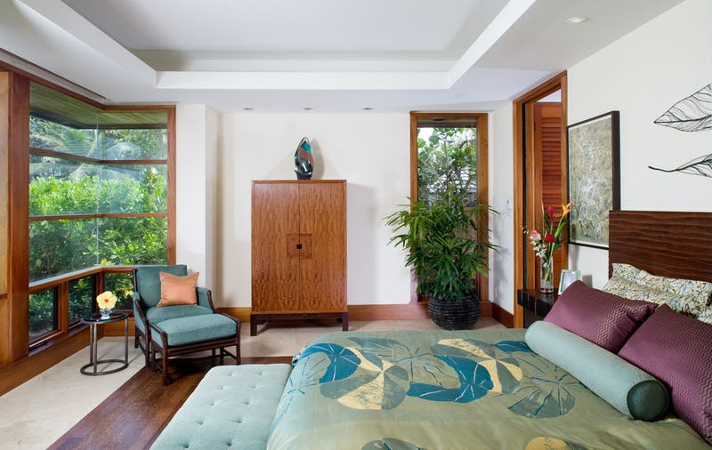 Bedroom with large window showing greenery