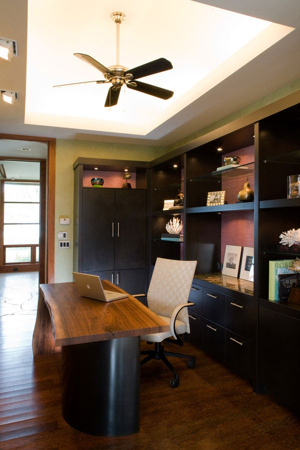 Office with wood desk and bookshelves in background