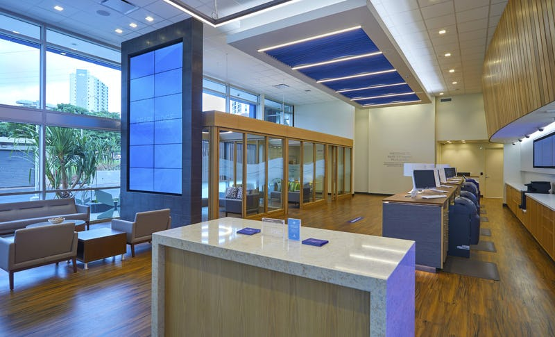Interior shot of Bank of Hawaii at Pearlridge showing wood floors, modern lighting, and glass conference rooms