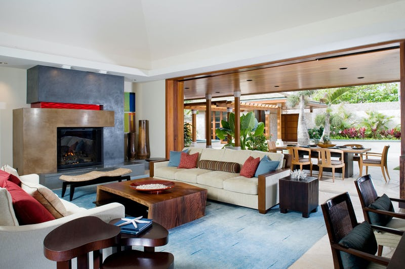 Living room with sofas, coffee table, and dining room in background