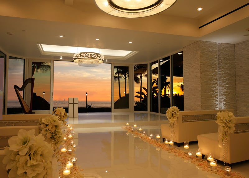 Chapel with flowers, candles, and view of a sunset.