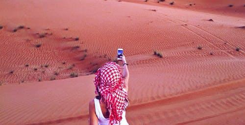 Meisje met mobieltje in woestijn van het Midden-Oosten