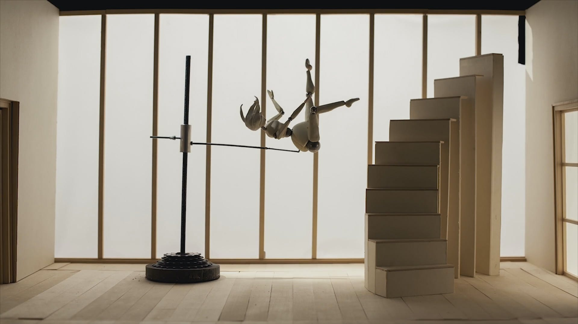 A stop-motion puppet in mid-fall from a staircase, held in pace by an armature.