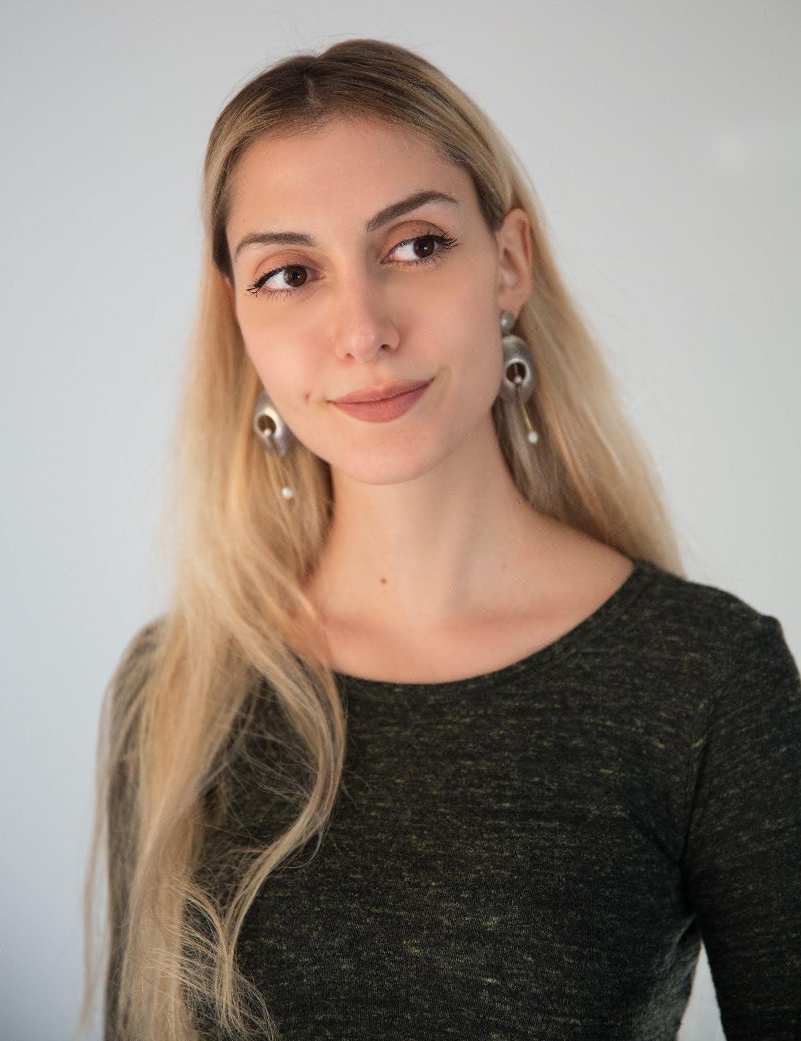 Blode girl with dark shirt smiling, wearing earings
