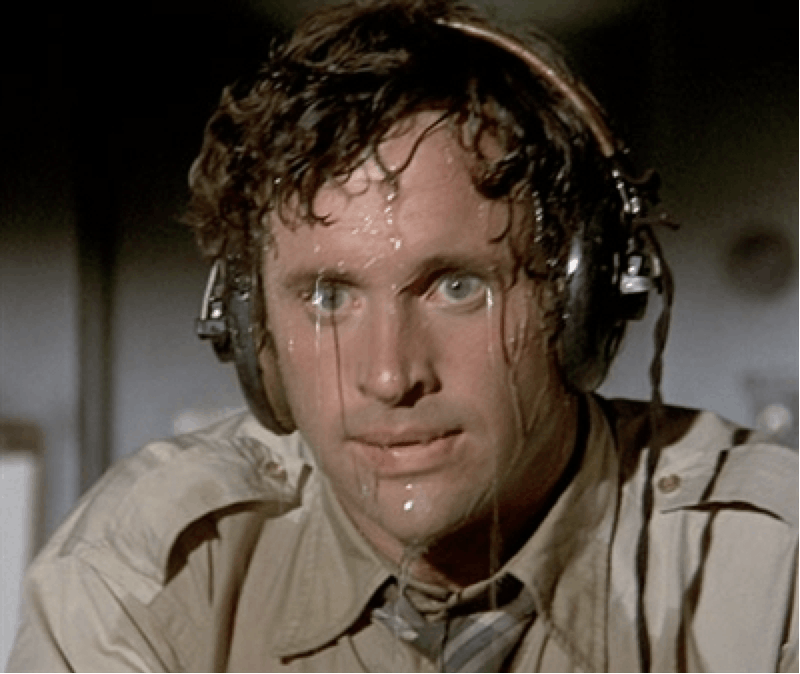 Military man, with curly hair, blue eyes, wearing headphones, that sweats