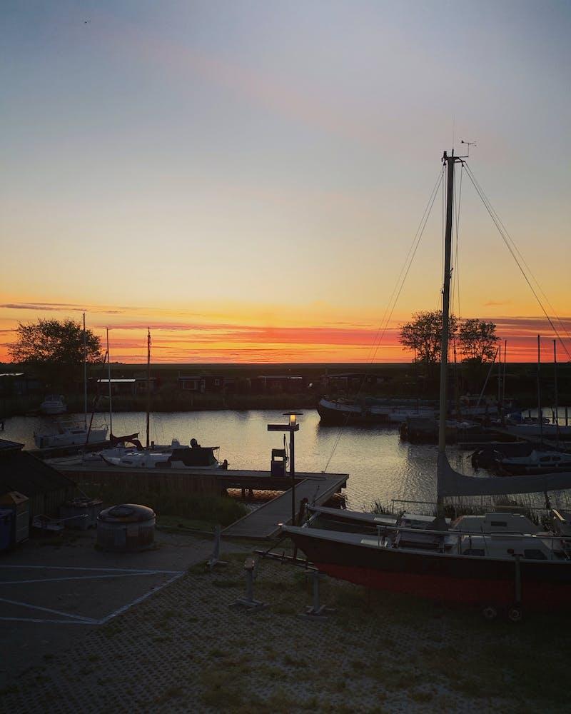 Het uitzicht van het restaurant over de haven aan met zonsondergang