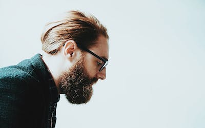 Man with glasses pondering