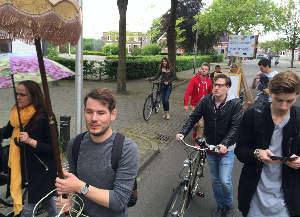 groep jongeren lopend over straat met fiets, bord en lamp