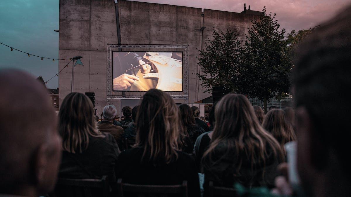 Groep mensen kijken naar een groot beeldscherm met een film erop.