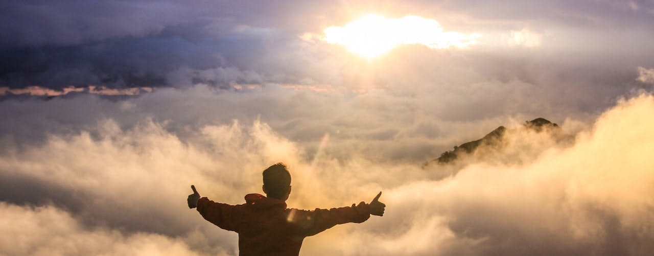 Man doing thumbs up standing on a mountain amongst the clouds