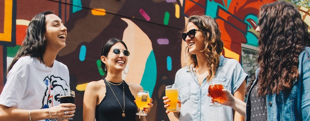 Women smiling and having a drink at festival