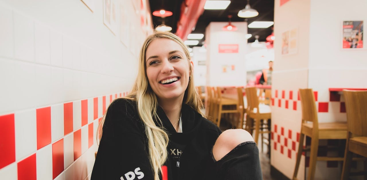 Blonde woman in restaurant smiling happily