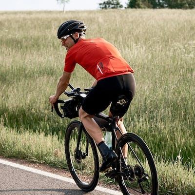 Road cyclist biking along a field