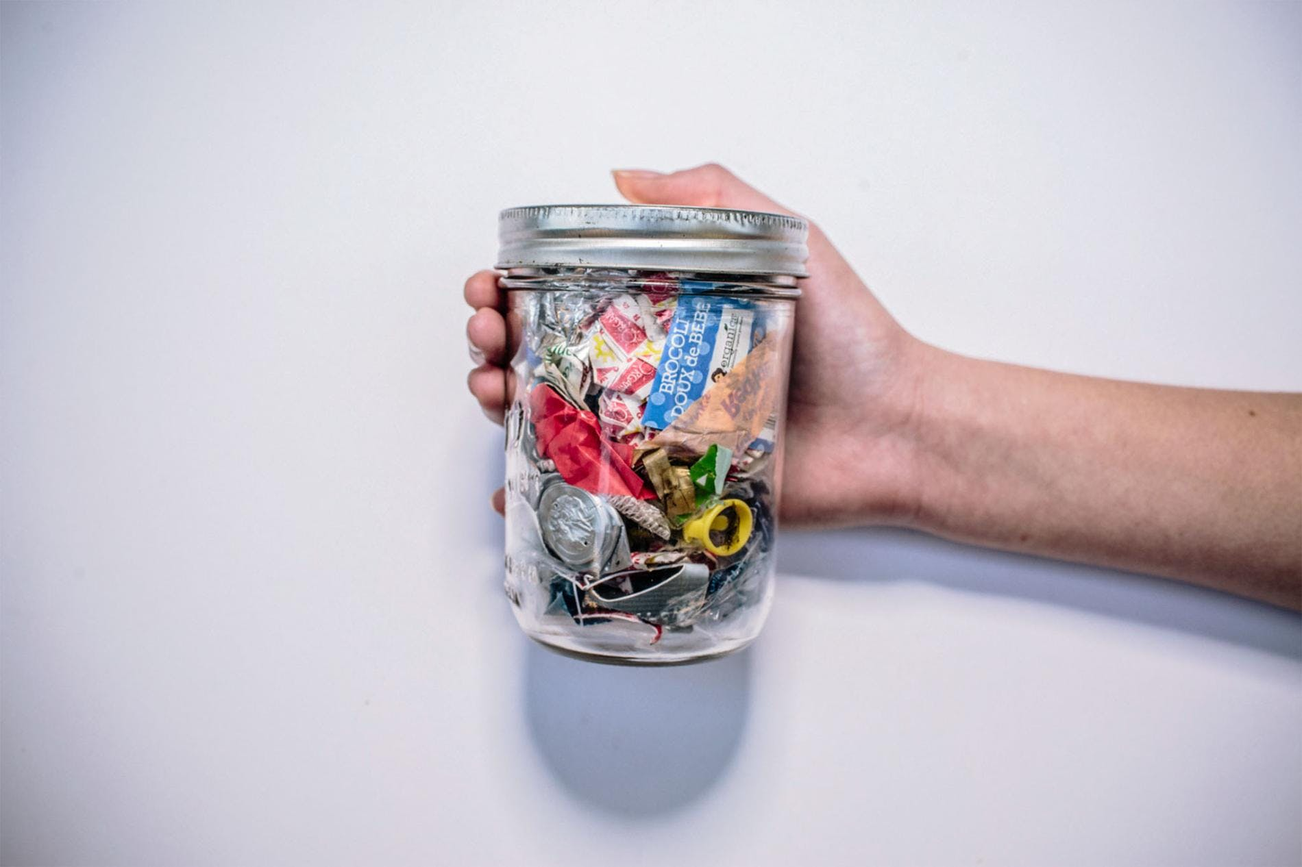A person holding waste on a glass jar