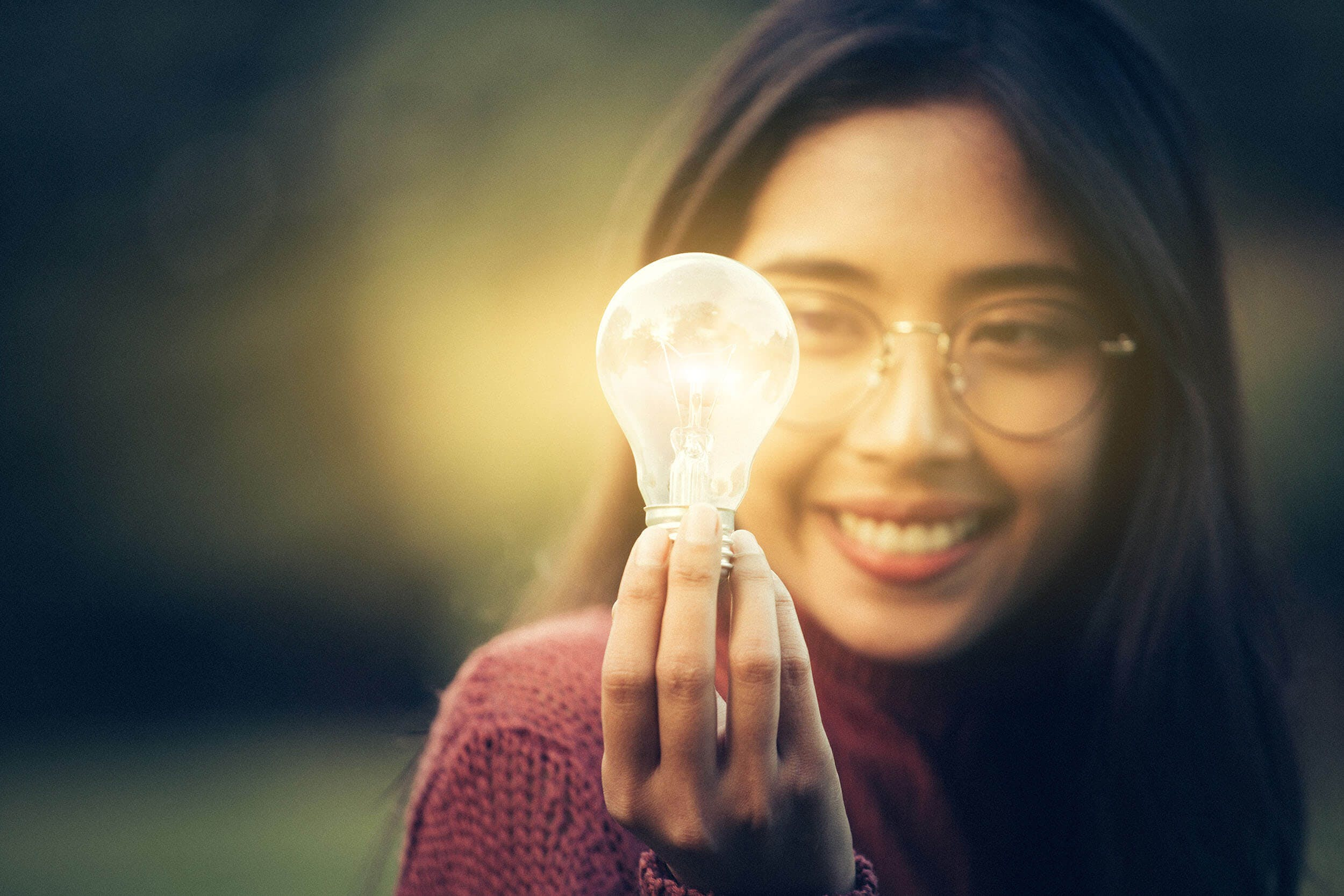 Woman cheerfully holds a lit light bulb
