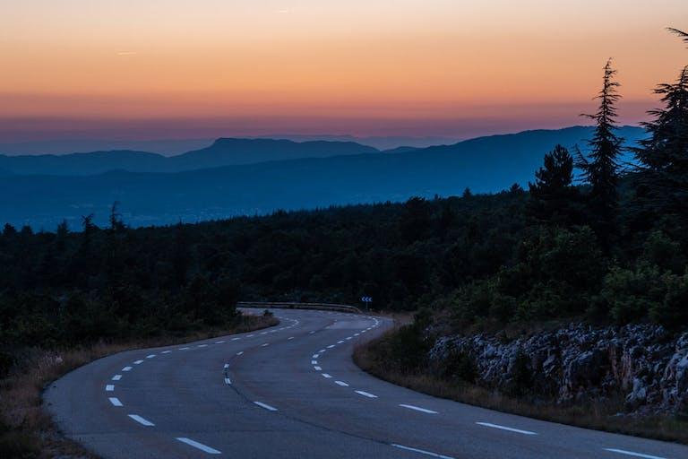 Straße in den Bergen bei Sonnenuntergang