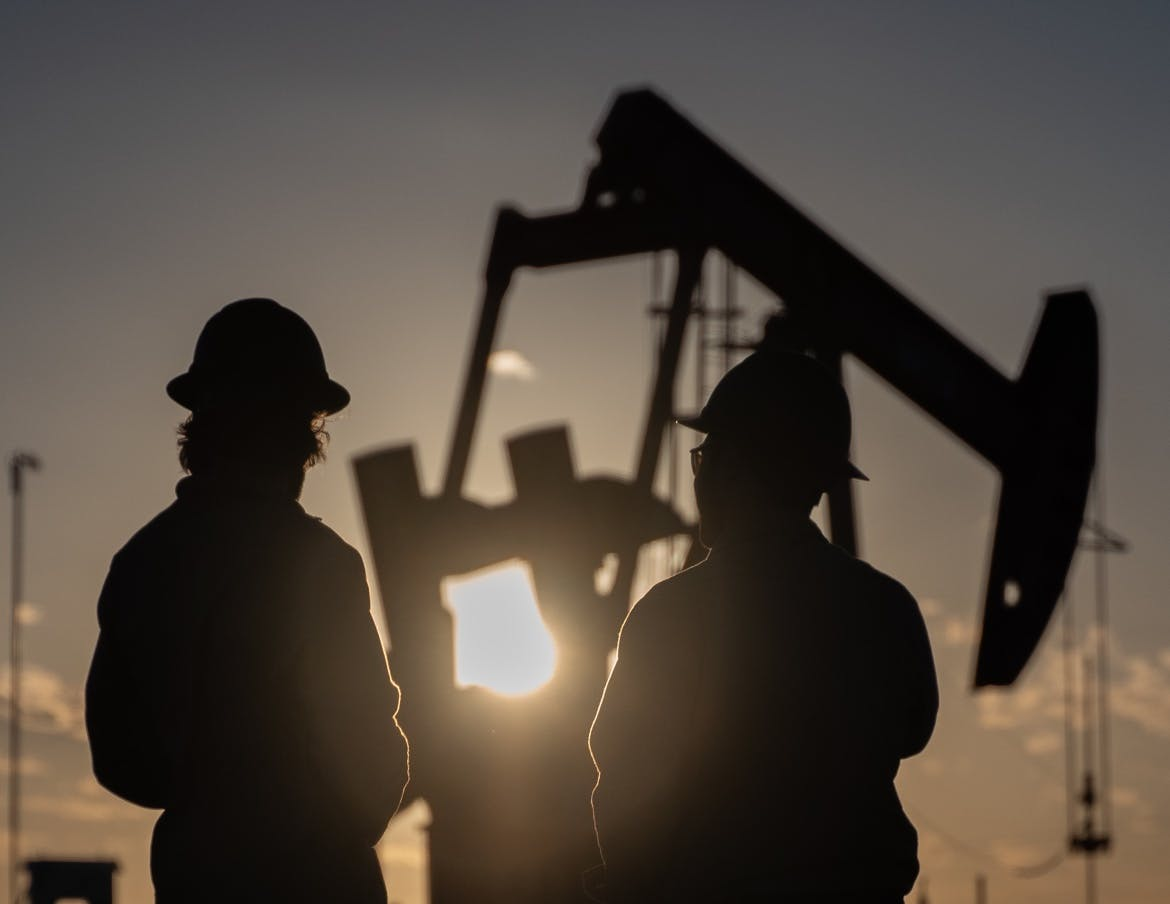 Two oilfield workers inspect a pump jack near sunset.