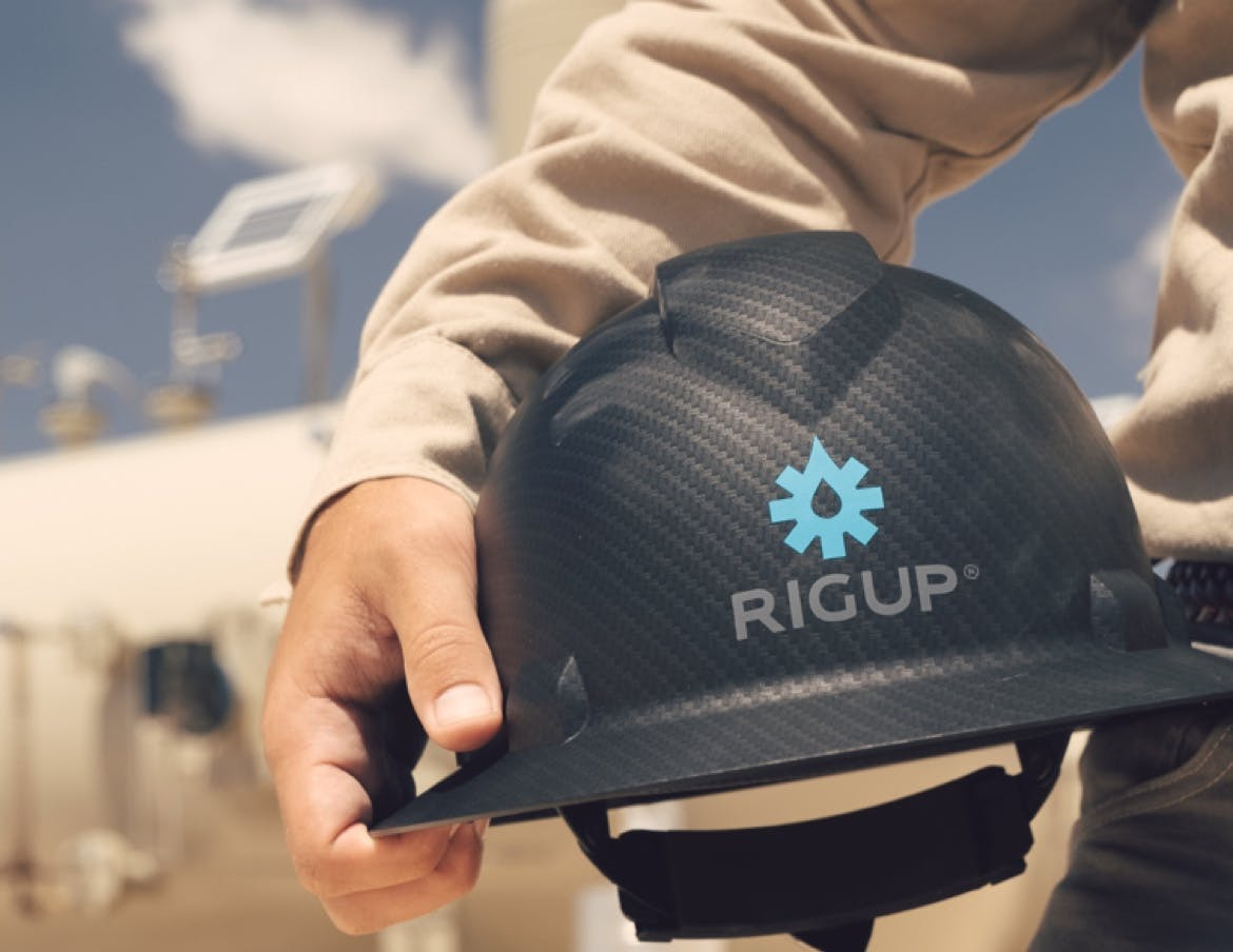 An oilfield contractor holds a hardhat with the RigUp logo on it.
