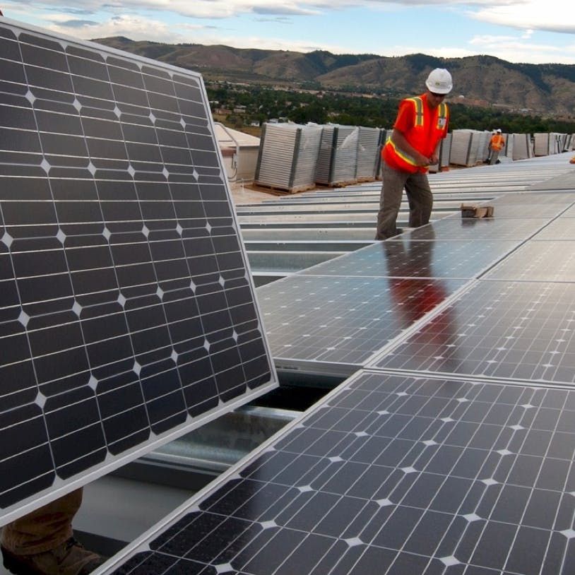Solar technicians install panels at an industrial solar site.