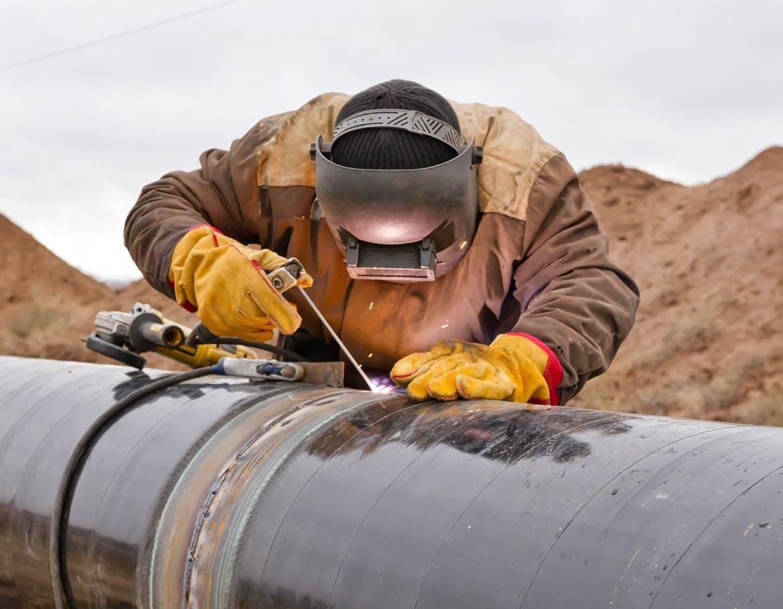 Pipeline welder repairing a pipeline joint.
