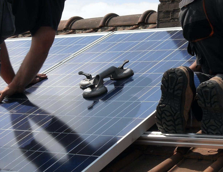 A solar technician installs a solar panel.